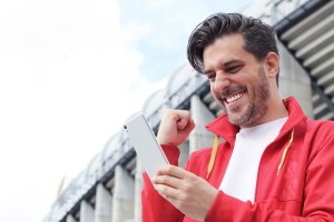 Man cheering on bet on mobile phone